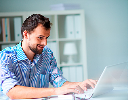 man smiling while using a laptop computer