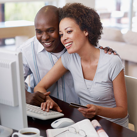 Man and woman smiling while looking at a computer
